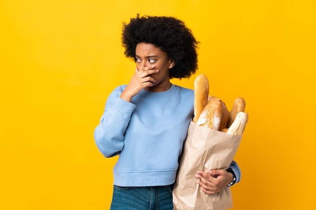 Giovane donna afroamericana che compra qualcosa di pane isolato sul giallo che fa gesto di sorpresa mentre guardando al lato