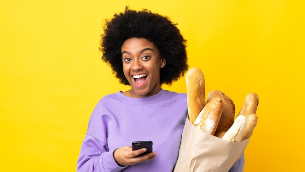 Giovane donna afroamericana che compra qualcosa di pane isolato su giallo sorpreso e invia un messaggio