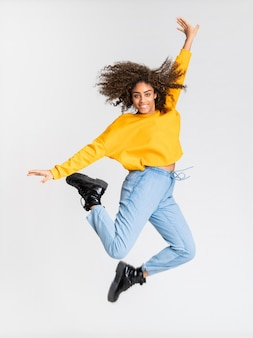 Giovane donna afroamericana che balla sopra la parete bianca