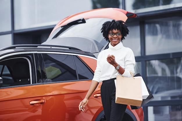 La giovane donna afroamericana in vetri sta all'aperto vicino all'automobile moderna dopo lo shopping con i pacchetti.