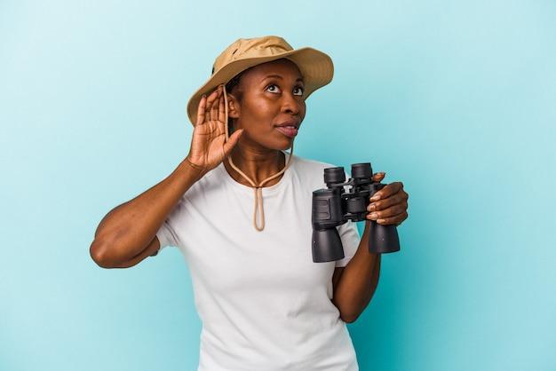 Giovane donna afroamericana che tiene il binocolo isolato su sfondo blu cercando di ascoltare un pettegolezzo.