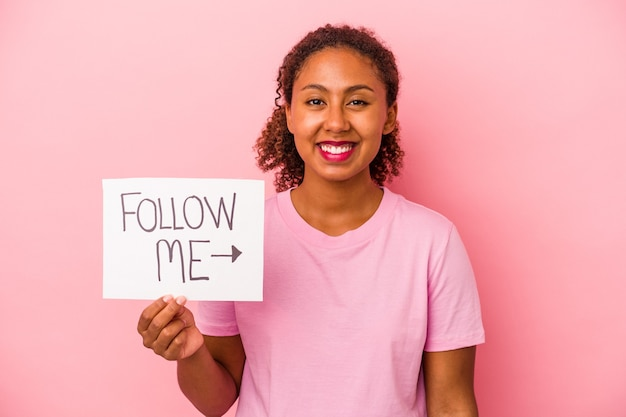 Giovane donna afroamericana che tiene un cartello seguimi isolato su sfondo rosa