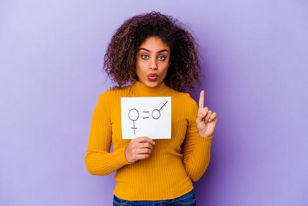Giovane donna afroamericana che tiene un cartello di uguaglianza di genere isolato sulla parete viola che ha qualche grande idea, concetto di creatività.