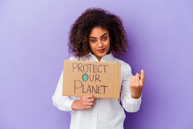 Giovane donna afroamericana che tiene un cartello di potere della ragazza isolato sul muro viola che punta con il dito contro di te come se invitando ad avvicinarsi