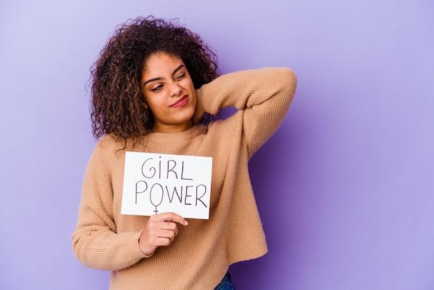 Giovane donna afroamericana che tiene un cartello di potere della ragazza isolato sulla parete viola che tocca la parte posteriore della testa, pensando e facendo una scelta
