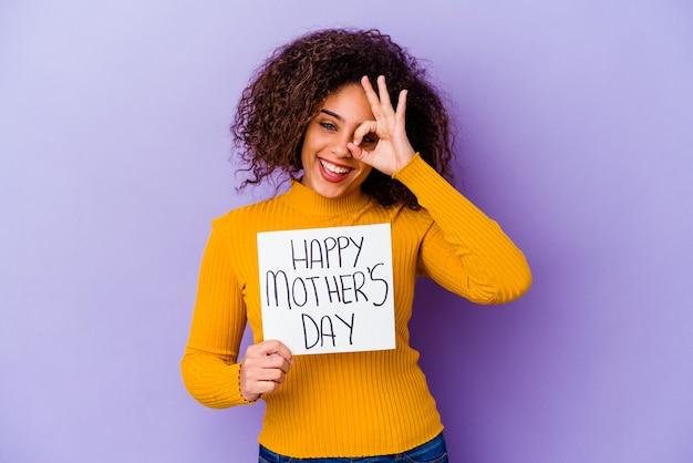Giovane donna afroamericana che tiene un cartello di festa della mamma felice isolato eccitato mantenendo il gesto giusto sull'occhio.