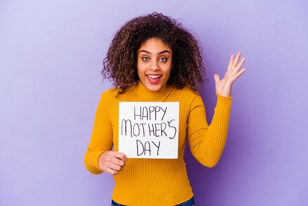 Giovane donna afroamericana che tiene un cartello di festa della mamma felice isolato ricevendo una piacevole sorpresa, eccitato e alzando le mani.