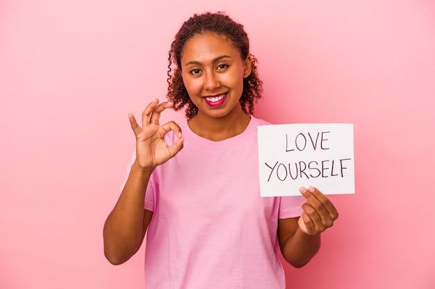 Giovane donna afroamericana che tiene cartello di amore te stesso isolato su sfondo rosa