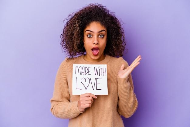 Giovane donna afroamericana che tiene un cartello fatto con amore isolato su sfondo viola sorpreso e scioccato.