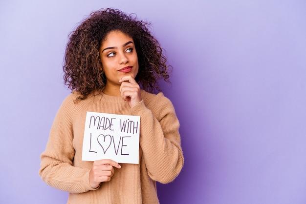 Giovane donna afroamericana che tiene un cartello made with love isolato sulla parete viola che guarda lateralmente con espressione dubbiosa e scettica
