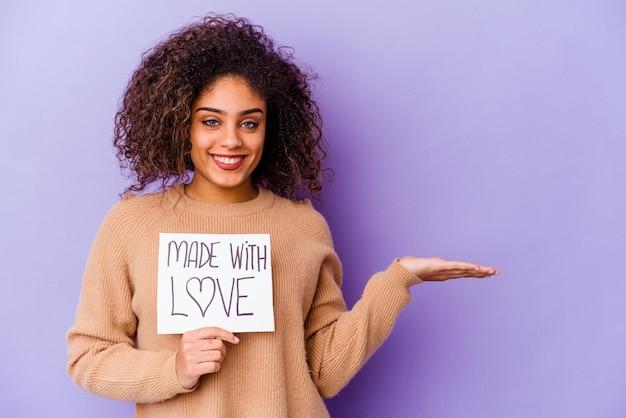Giovane donna afroamericana che tiene un cartello made with love isolato sul muro viola che mostra uno spazio di copia su un palmo e che tiene un'altra mano sulla vita.
