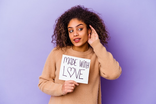 Giovane donna afroamericana che tiene un cartello made with love isolato sulla parete viola, cercando di ascoltare un pettegolezzo