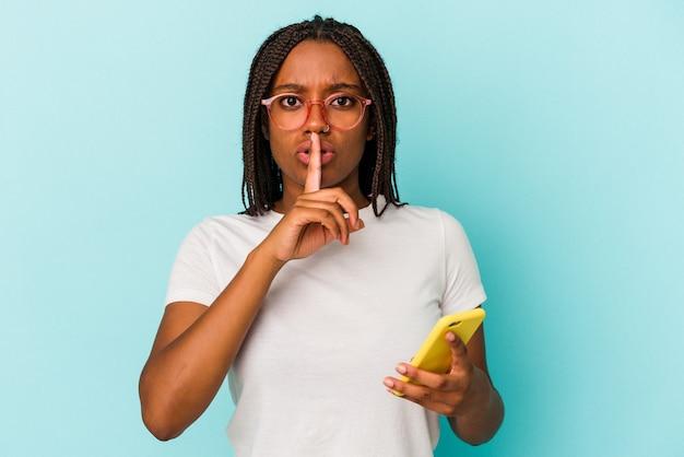 Giovane donna afroamericana in possesso di un telefono cellulare isolato su sfondo blu mantenendo un segreto o chiedendo silenzio.