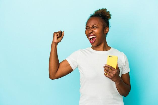 Giovane donna afroamericana che tiene un telefono cellulare isolato su fondo blu che alza il pugno dopo una vittoria, concetto del vincitore.