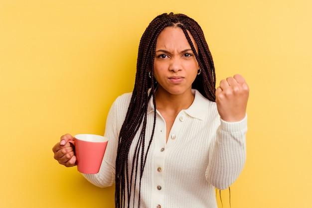 Giovane donna afroamericana che tiene una tazza isolata che mostra il pugno alla macchina fotografica, espressione facciale aggressiva.