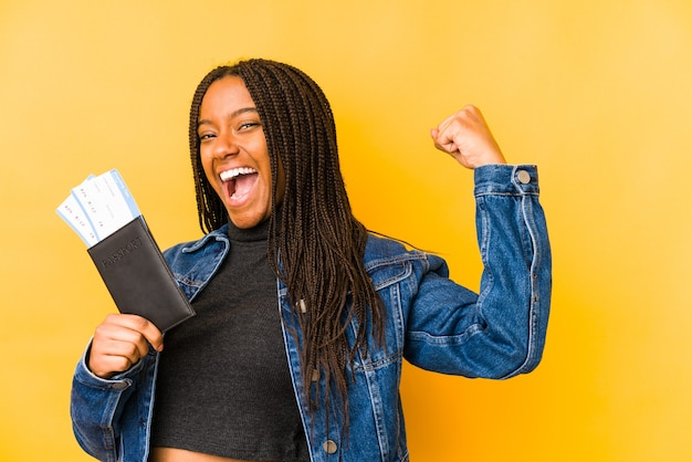 Giovane donna afroamericana che tiene un passaporto isolato alzando il pugno dopo una vittoria, concetto di vincitore.
