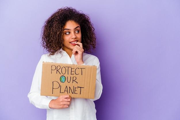 Giovane donna afroamericana che tiene un banner di proteggere il nostro pianeta