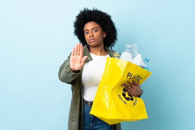 La giovane donna afroamericana che tiene una borsa di riciclaggio sulla parete variopinta che fa il gesto di arresto