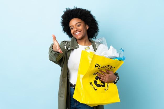Giovane donna afroamericana che tiene una borsa di riciclaggio sulla parete colorata che stringe la mano per chiudere un buon affare