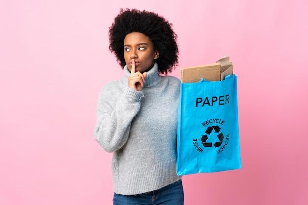 Giovane donna afroamericana che giudica una borsa di riciclaggio isolata su fondo variopinto che mostra un segno di gesto di silenzio che mette il dito in bocca