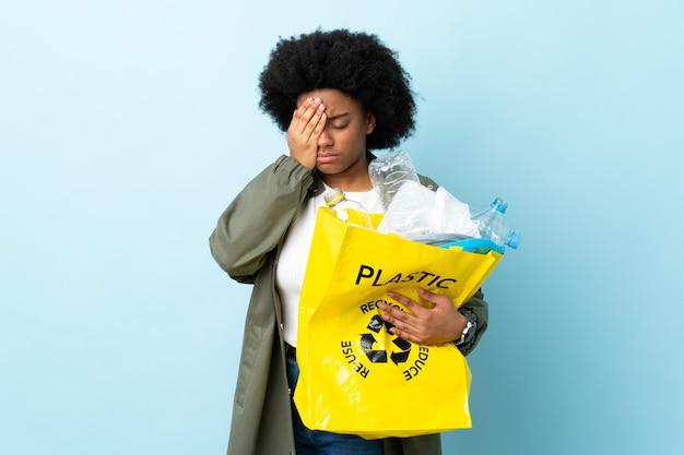 Giovane donna afro-americana in possesso di un sacchetto di riciclo isolato su occhi colorati coning con le mani