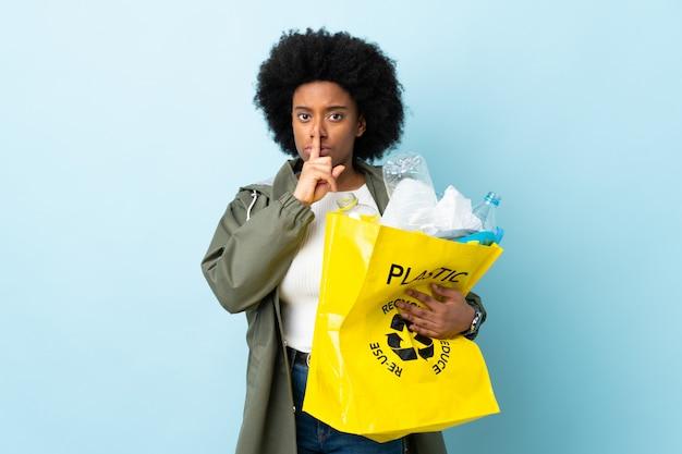 Giovane donna afroamericana che giudica una borsa di riciclaggio isolata sulla mostra variopinta un segno del gesto di silenzio che mette il dito in bocca