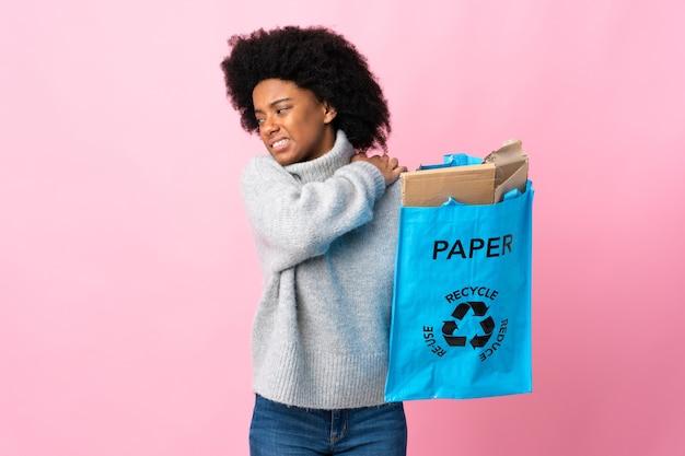 Giovane donna afro-americana in possesso di un sacchetto di riciclaggio isolato su colorato che soffre di dolore alla spalla per aver fatto uno sforzo