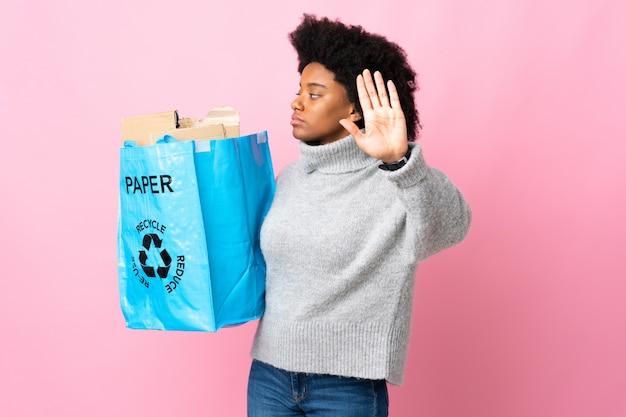 Giovane donna afroamericana che giudica una borsa di riciclaggio isolata sulla parete variopinta che fa gesto di arresto e deludente