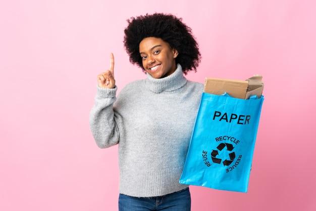 Giovane donna afroamericana che tiene un sacchetto di riciclaggio che mostra e che solleva un dito in segno del meglio