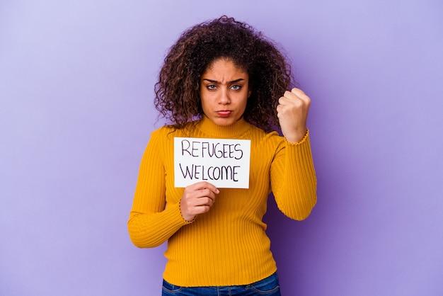Giovane donna afroamericana in possesso di un cartello di benvenuto per i rifugiati isolato che mostra il pugno alla telecamera, espressione facciale aggressiva.