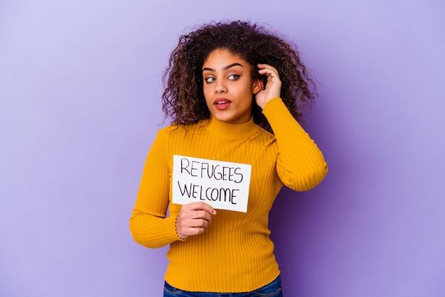 La giovane donna afroamericana che tiene un cartello di benvenuto dei rifugiati ha isolato il tentativo di ascoltare un pettegolezzo