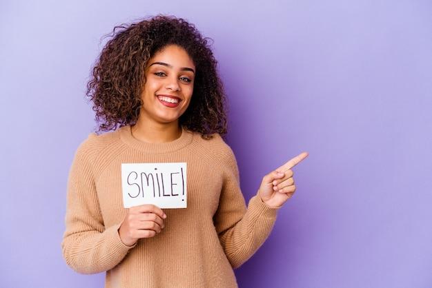 Giovane donna afroamericana che tiene un cartello di sorriso isolato sulla parete viola che sorride e che indica da parte, mostrando qualcosa nello spazio vuoto