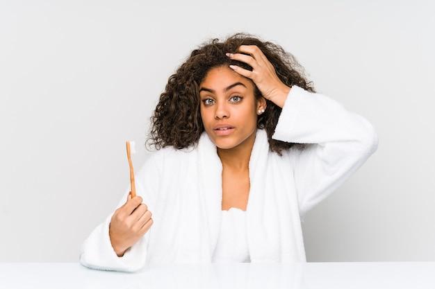 Giovane donna afroamericana che tiene uno spazzolino da denti scioccata, ha ricordato un incontro importante.
