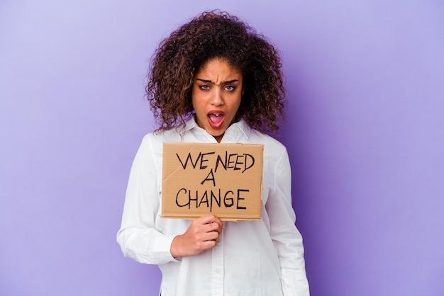 Giovane donna afroamericana in possesso di un abbiamo bisogno di un banner di cambiamento