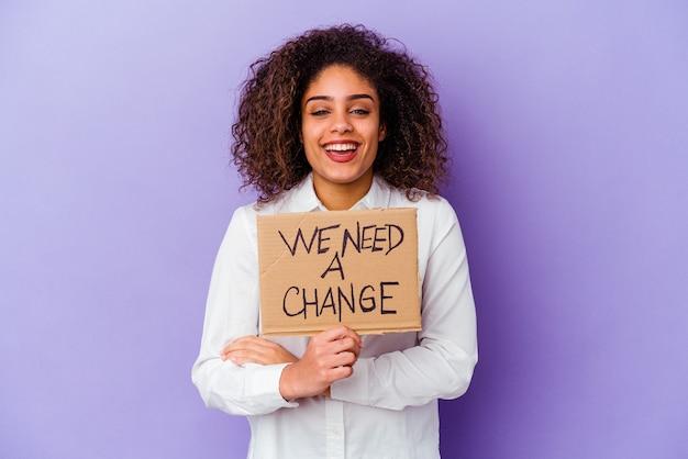 Giovane donna afro-americana in possesso di un abbiamo bisogno di un cartello di cambiamento isolato sulla parete viola ridendo e divertendosi