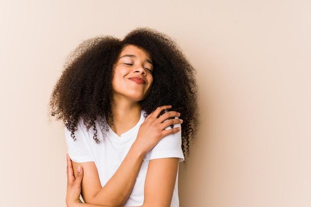 Abbracci di giovane donna afro-americana, sorridente spensierato e felice.