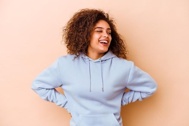 La giovane donna afroamericana isolata su fondo beige ride e chiude gli occhi, si sente rilassata e felice.