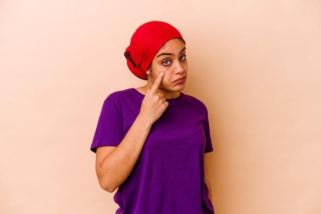 Giovane donna afro-americana isolata sul muro beige piangere, insoddisfatta di qualcosa