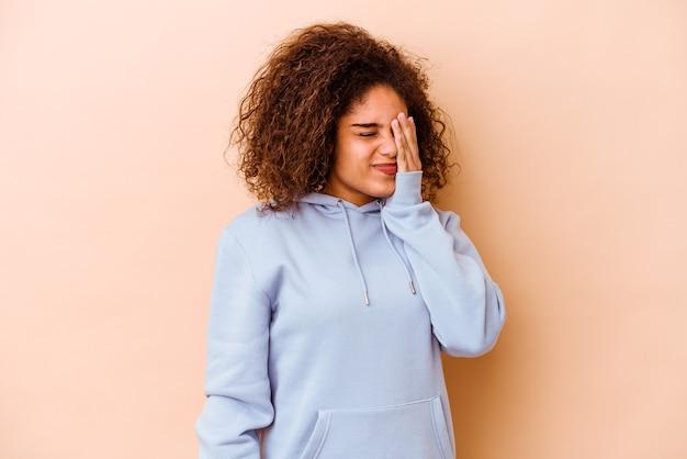 Giovane donna afro-americana isolata sul muro beige con mal di testa, toccando la parte anteriore del viso