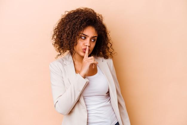 Giovane donna afroamericana isolata sulla parete beige mantenendo un segreto o chiedendo silenzio