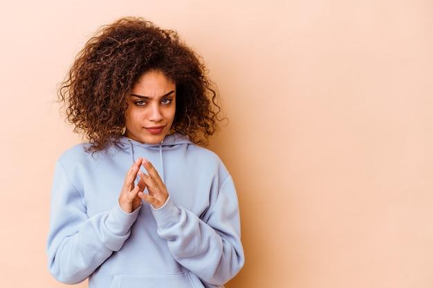 Giovane donna afro-americana isolata sulla parete beige che compongono il piano in mente, creando un'idea