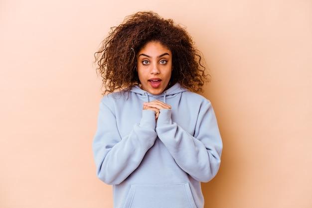 Giovane donna afroamericana isolata sulla parete beige che prega per fortuna, bocca stupita e di apertura che osserva alla parte anteriore