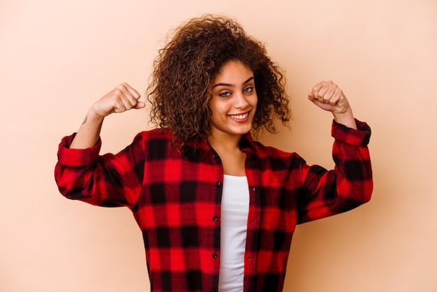 Giovane donna afroamericana isolata sulla parete beige che mostra il gesto di forza con le braccia