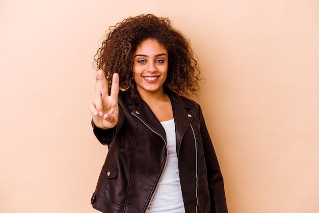 Giovane donna afroamericana isolata sulla parete beige che mostra il segno di vittoria e che sorride ampiamente.