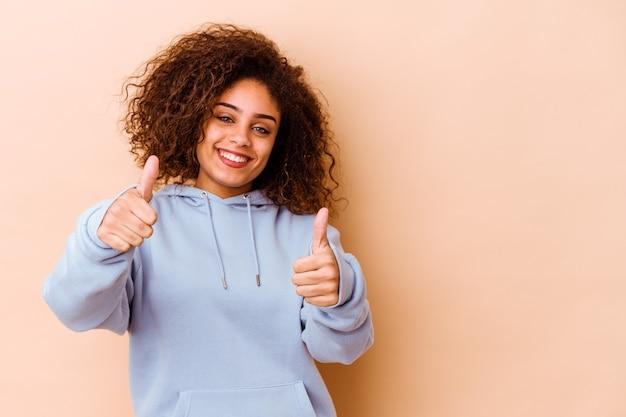 Giovane donna afroamericana isolata sulla parete beige che sorride e che alza il pollice in su
