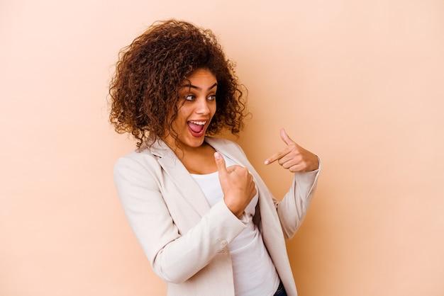Giovane donna afroamericana isolata sul muro beige sorpreso indicando con il dito, sorridendo ampiamente.