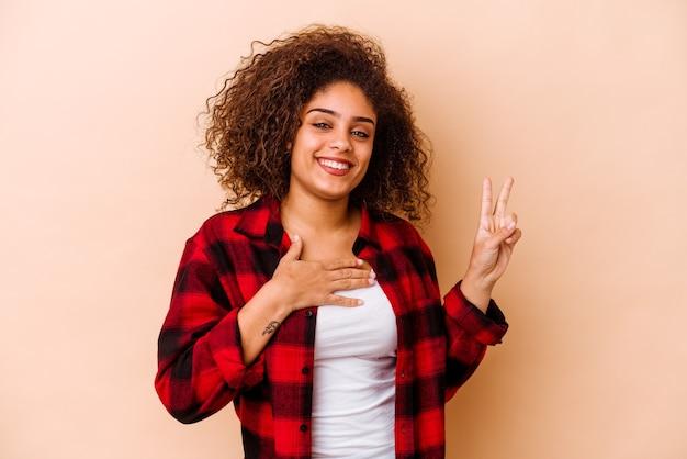 Giovane donna afroamericana isolata sul muro beige prestando giuramento, mettendo la mano sul petto