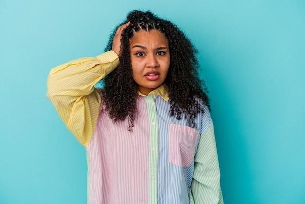 Giovane donna afroamericana isolata su sfondo blu scioccata, ha ricordato un incontro importante.