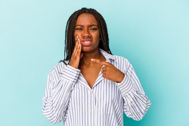 Giovane donna afroamericana isolata su fondo blu che ha un forte dolore dei denti, dolore molare.