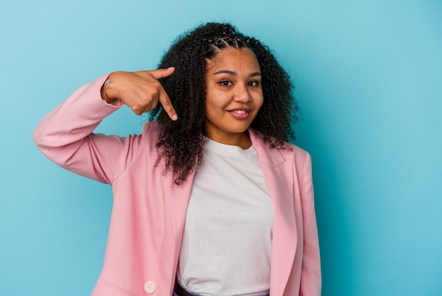 Giovane donna afroamericana isolata su sfondo blu persona che indica a mano uno spazio copia camicia, orgogliosa e fiduciosa